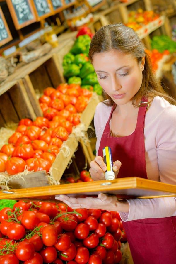 Assistente de loja que escreve a placa do preço imagem de stock