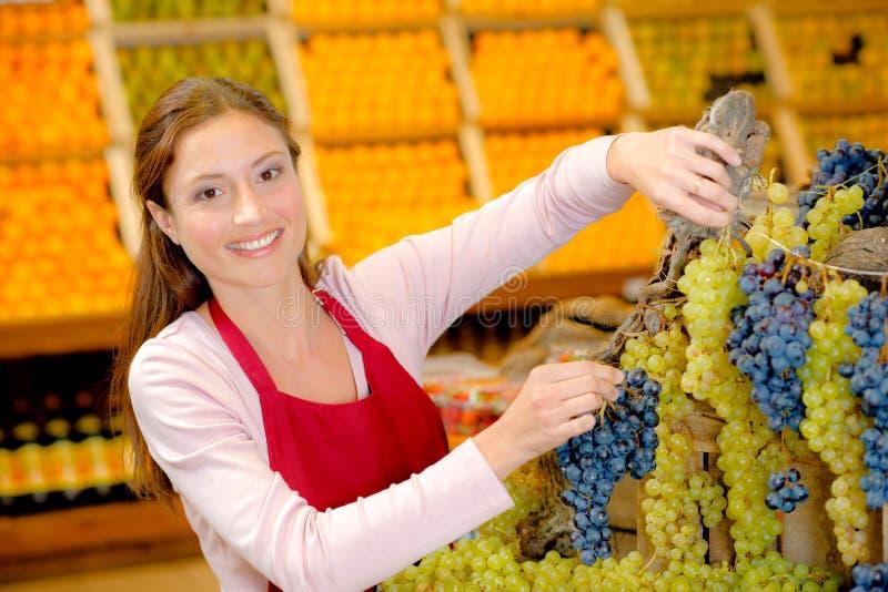Assistente de loja que faz a exposição com uvas imagem de stock