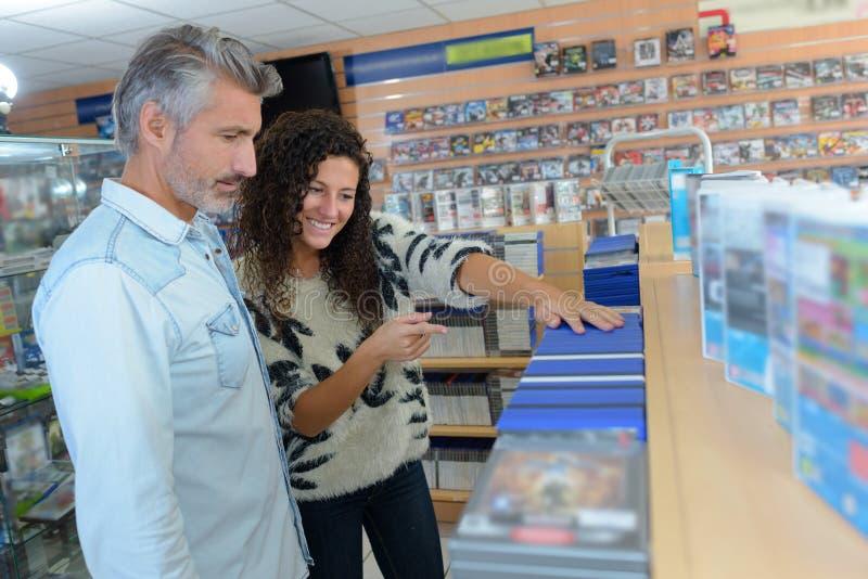 Assistente de loja que mostra jogos de computador ao cliente masculino fotos de stock