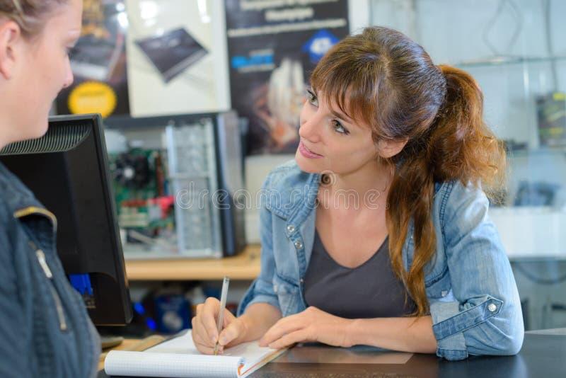 Assistente de loja que toma notas do cliente imagens de stock