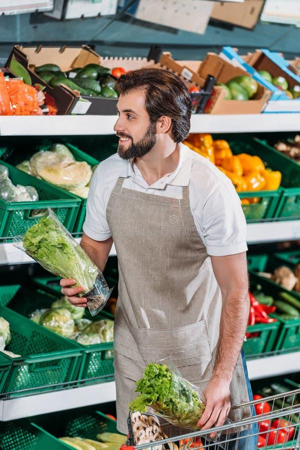 assistente de loja de sorriso que arranja legumes frescos fotografia de stock