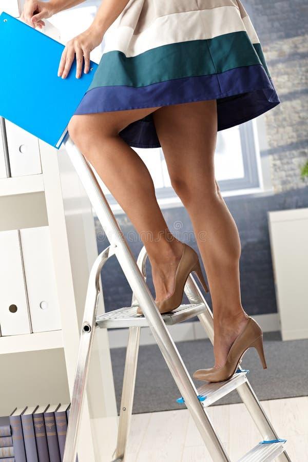 Assistente dell'ufficio sulla scaletta con il dispositivo di piegatura fotografie stock libere da diritti