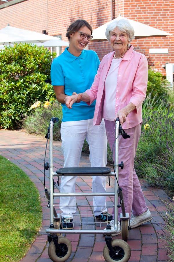 Assistente di cura che aiuta una signora anziana fotografia stock