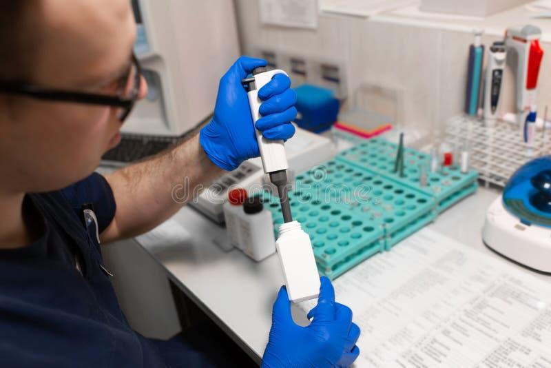 Assistente di laboratorio che analizza un campione di sangue facendo uso della micropipetta fotografie stock