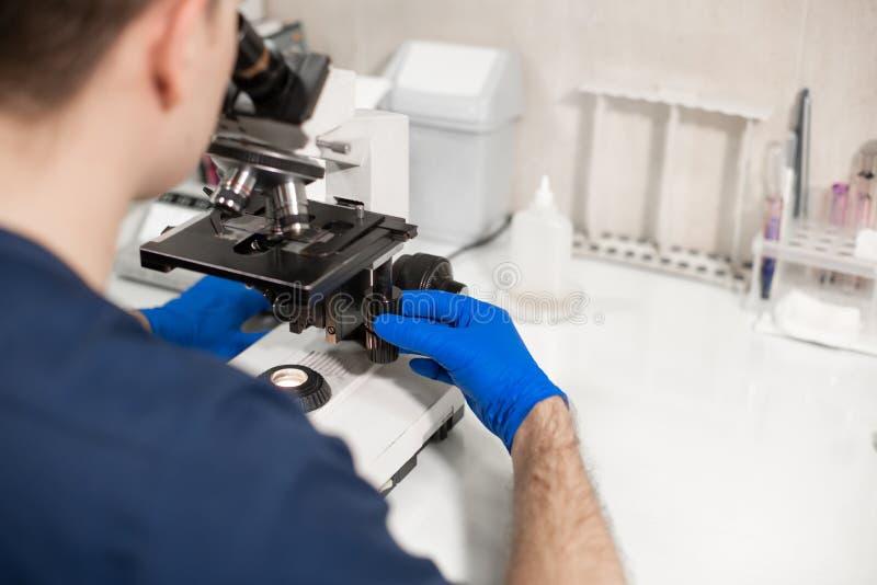 Assistente di laboratorio che guarda tramite il microscopio r Scienza e concetto della medicina immagini stock