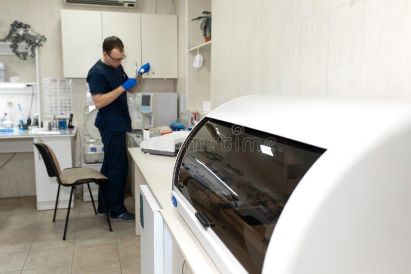 Assistente di laboratorio fare il sangue della prova nell'analizzatore automatico del campione di sangue fotografia stock libera da diritti