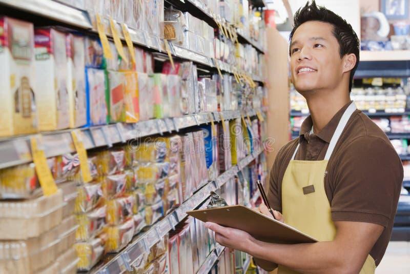 Assistente di vendite che fa uno stocktake fotografia stock