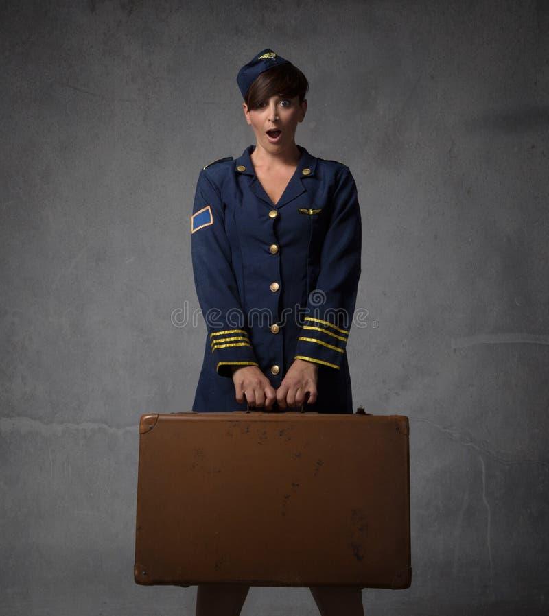 Assistente di volo con la valigia ed il fronte sorprendente immagini stock libere da diritti