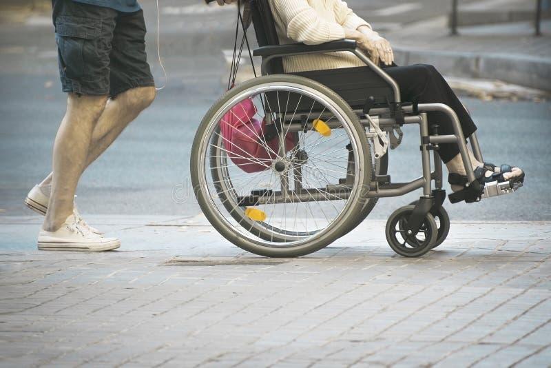 Assistente do homem novo que empurra uma mulher adulta que senta-se em uma cadeira de rodas Inabilidades e conceito da desvantage foto de stock royalty free