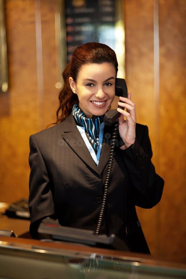 Assistente fêmea à moda na recepção do hotel foto de stock