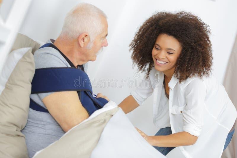 Assistente femminile sorridente con l'uomo senior sul letto a casa fotografia stock libera da diritti