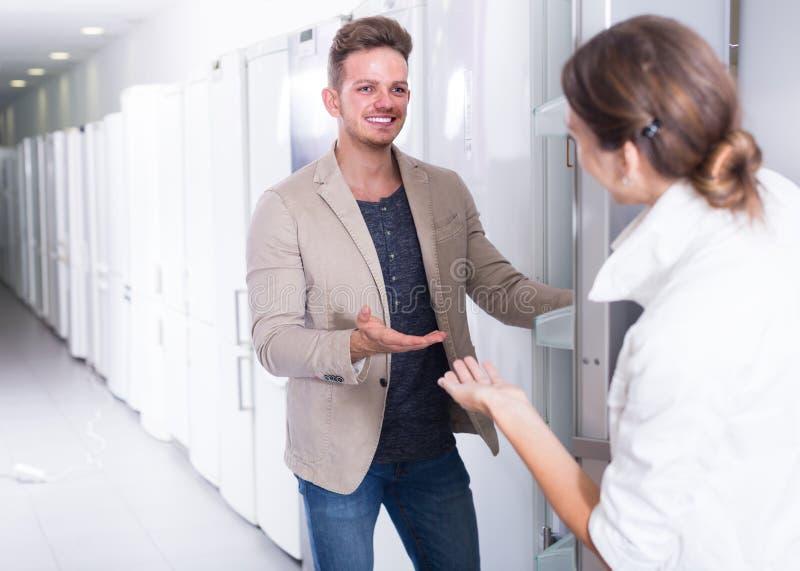 Assistente na venda da loja um refrigerador ao cliente alegre fotografia de stock royalty free