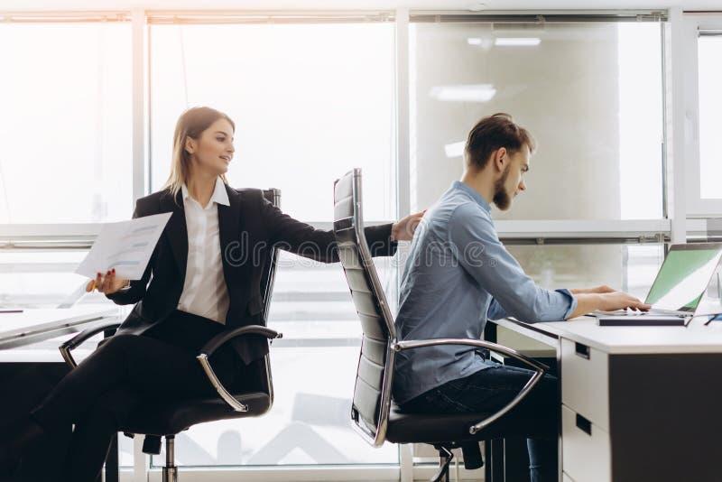 Assistente pessoal de sorriso novo que dá o documento ao trabalhador de escritório em seu escritório, contador fêmea que relata o imagem de stock
