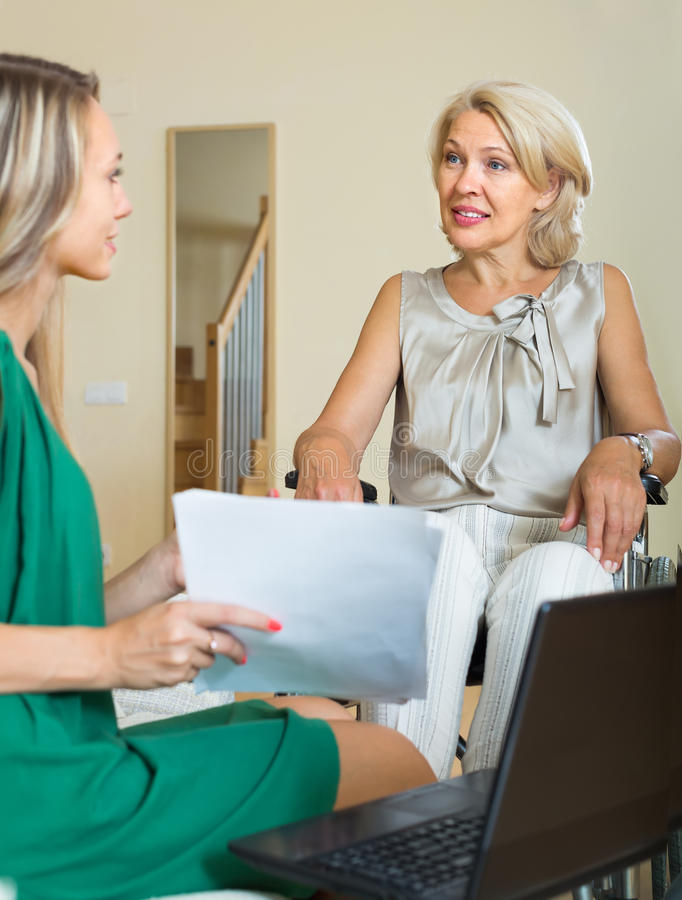 Assistente sociale e donna handicappata con il computer portatile immagini stock libere da diritti