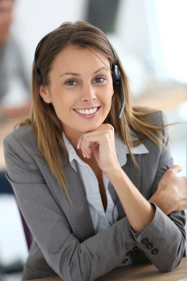 Assistente sorridente di servizio di assistenza al cliente sul lavoro immagini stock libere da diritti