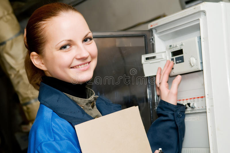 Assistente tecnico allegro della donna in una caldaia fotografia stock libera da diritti