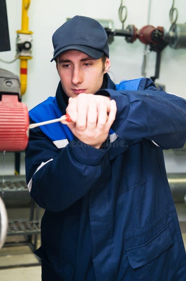 Assistente tecnico del riscaldamento nel locale caldaie immagini stock