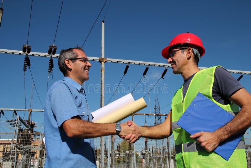 Assistente tecnico ed operaio alla sottostazione elettrica immagini stock
