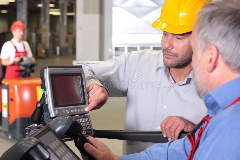 Assistente tecnico ed operaio maggiore al pannello di controllo immagini stock libere da diritti