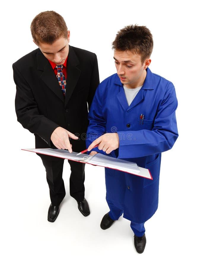 Assistente tecnico ed uomo d'affari che indicano al taccuino fotografia stock libera da diritti