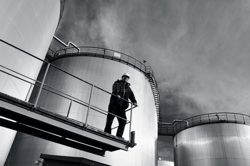 Assistente tecnico nei serbatoi dell'olio e dell'elmetto protettivo immagini stock libere da diritti