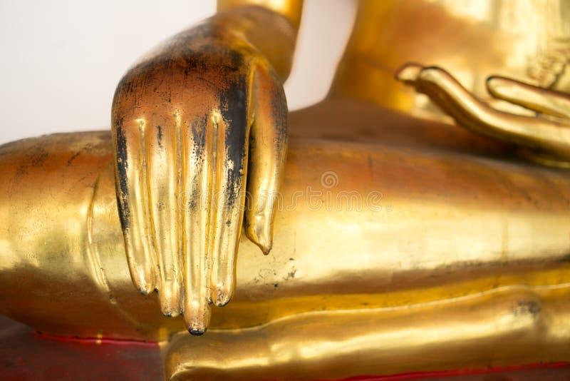 Assistenten av Buddhastatyn för gammal guld sitter det lade benen på ryggen korset arkivfoton