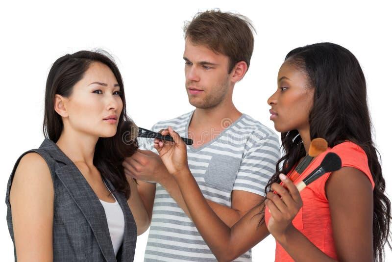 Assistenter som applicerar smink till den kvinnliga modellen arkivfoto