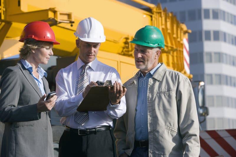 Assistenti tecnici di costruzione che catturano le note fotografia stock