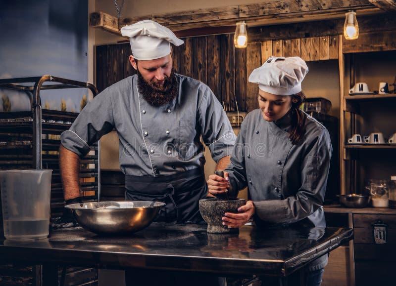 Assistentkocken maler sesamfrö i en mortel för att laga mat bröd Kock som undervisar hans assistent att baka brödet i arkivfoto