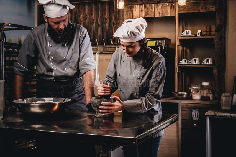 Assistentkocken maler sesamfrö i en mortel för att laga mat bröd Kock som undervisar hans assistent att baka brödet i arkivbilder