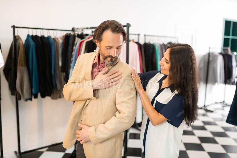 Beautiful radiant alluring stylist helping a adult attractive male royalty free stock image