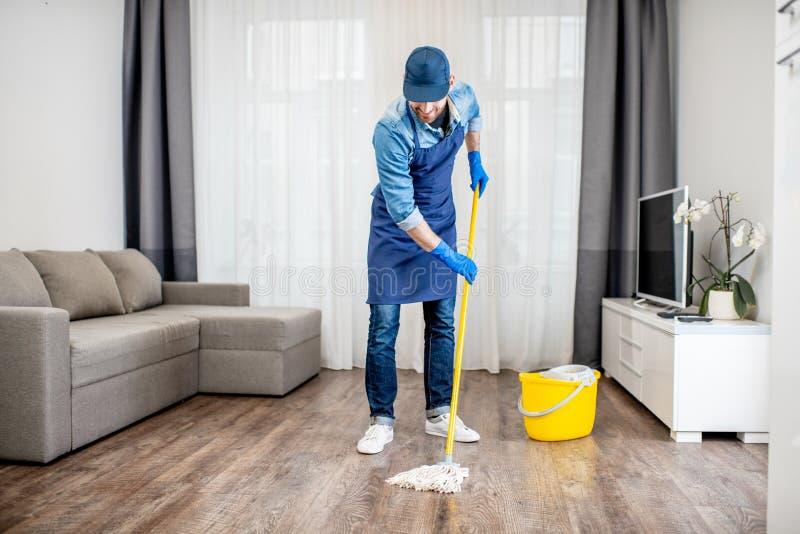 Assoalho da lavagem do homem no apartamento fotos de stock