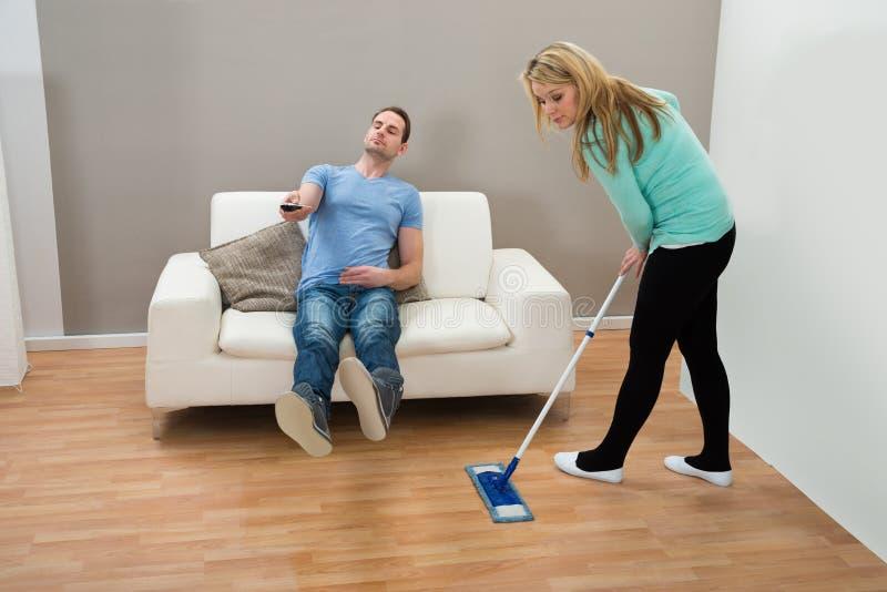 Assoalho da limpeza da mulher quando homem no sofá imagens de stock