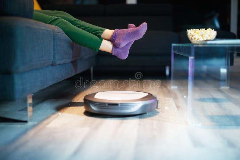 Assoalho da limpeza do robô quando a criança olhar o filme da tevê foto de stock