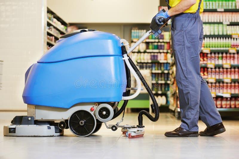 Assoalho da limpeza do trabalhador com máquina fotografia de stock