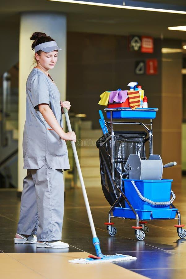 Assoalho da limpeza do trabalhador com máquina fotografia de stock royalty free