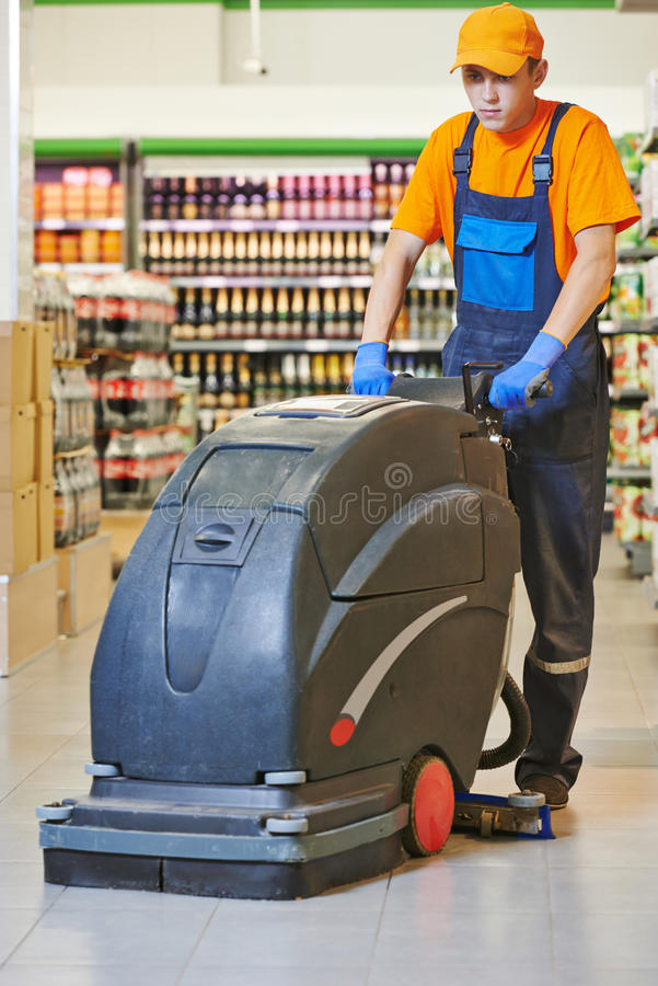 Assoalho da loja da limpeza do trabalhador com máquina fotografia de stock royalty free