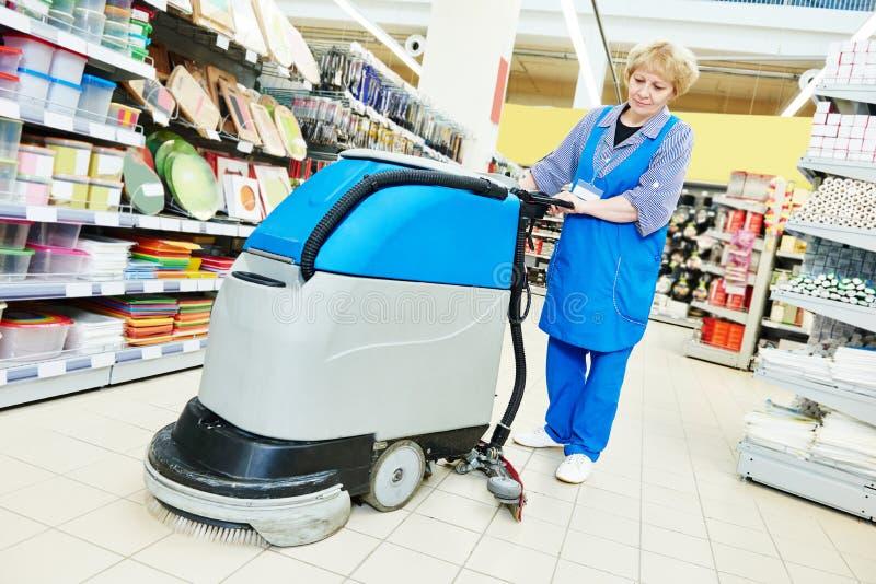Assoalho da loja da limpeza do trabalhador com máquina imagem de stock royalty free