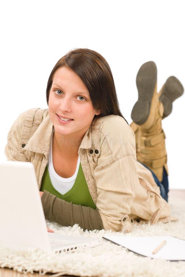 Assoalho de encontro de dactilografia do portátil da menina do adolescente do estudante imagens de stock
