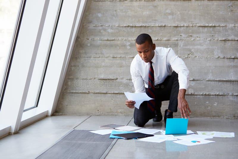 Assoalho de Laying Documents On do homem de negócios para planejar o projeto foto de stock royalty free