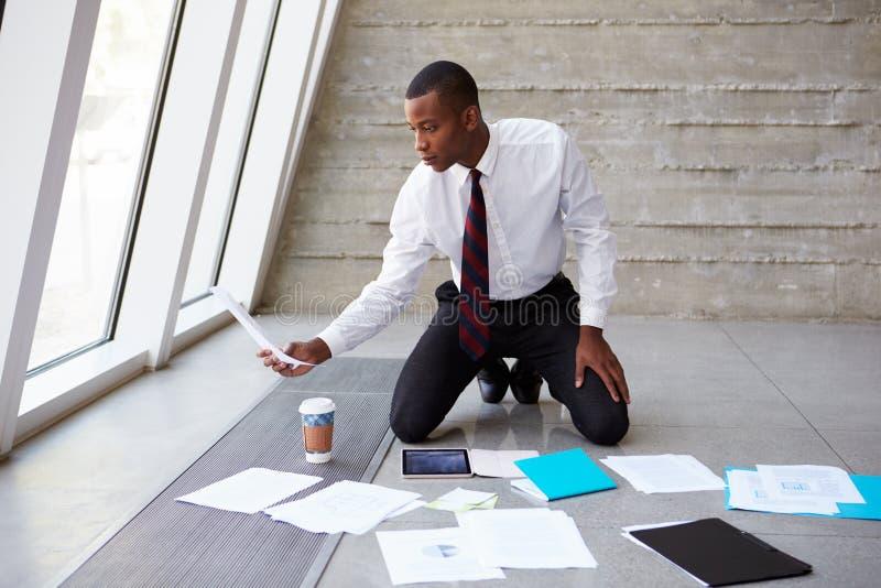 Assoalho de Laying Documents On do homem de negócios para planejar o projeto fotos de stock royalty free