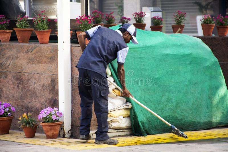 Assoalho de limpeza do líquido de limpeza indiano do trabalhador dos homens no jardim do parque do pátio do armazém na manhã da c imagem de stock royalty free