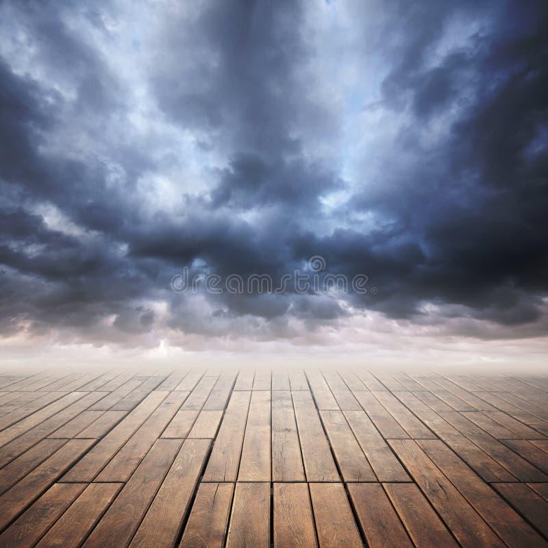 Assoalho de madeira com perspectiva e o céu tormentoso ilustração royalty free