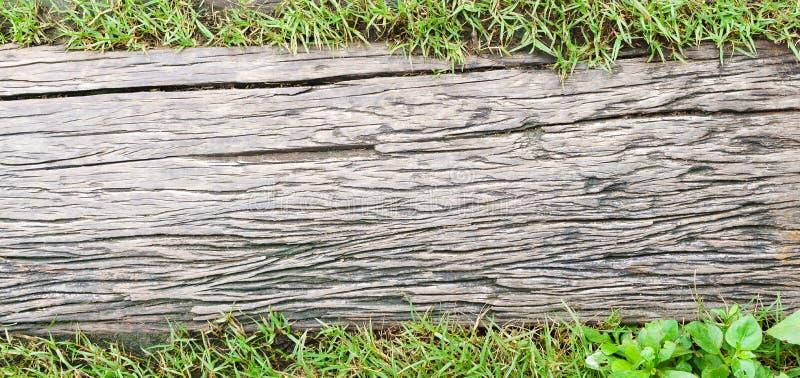 Assoalho de madeira do Grunge para o fundo da passagem com campo de grama verde, imagens de stock royalty free