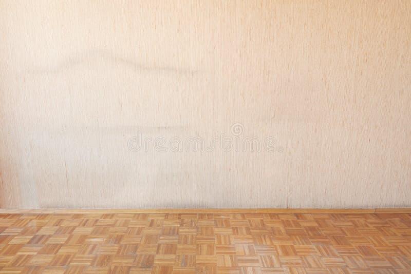 Assoalho de madeira velho no interior vazio da sala com tapeçaria bege imagens de stock
