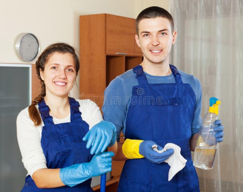Assoalho de sorriso da limpeza da equipe dos líquidos de limpeza fotografia de stock
