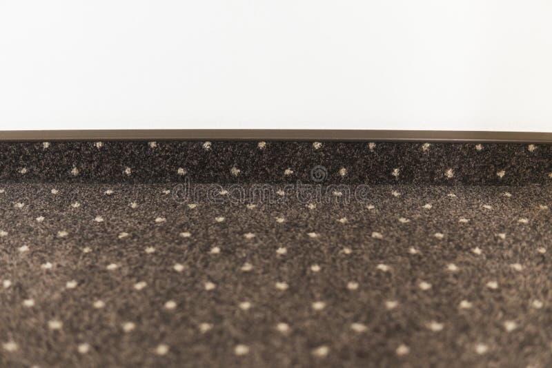 Assoalho de tapete de Brown com pontos brancos com um rodapé do tapete em uma parede branca fotografia de stock