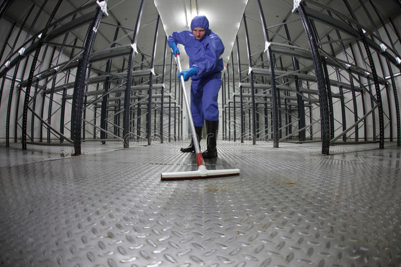 Assoalho uniforme da limpeza do trabalhador no storehouse imagens de stock royalty free