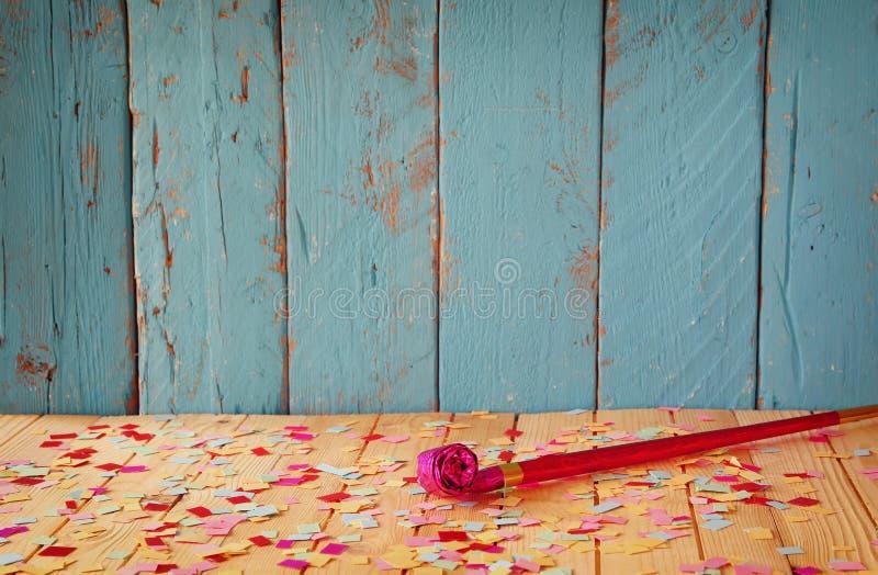 Assobio cor-de-rosa do partido na tabela de madeira com confetes coloridos imagem filtrada vintage imagens de stock