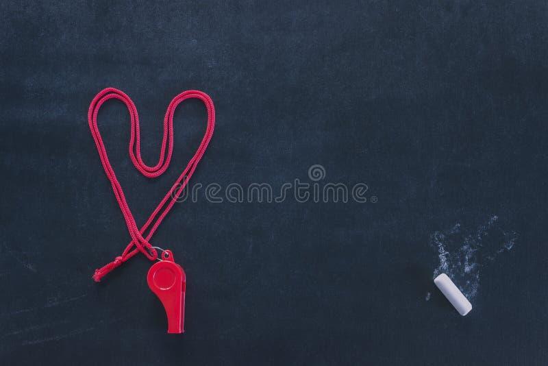 Assobio dos esportes em um laço vermelho Apresentado na forma de um coração Parte do giz branco Competição de esporte do conceito foto de stock royalty free